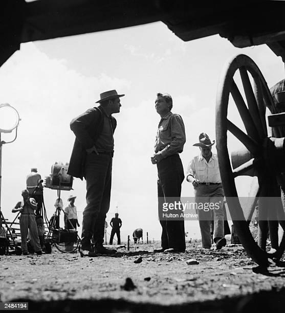 Lowangle shot of American actors Van Heflin and Alan Ladd speaking on the set of the film 'Shane' directed by George Stevens 1953 Crew members work...