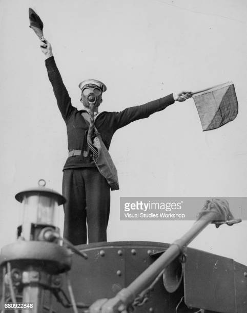 Lowangle view of a sailor in a gas mask as he uses semaphore flags to send a message from the HMS Furious aircraft carrier at sea 1920s or 1930s