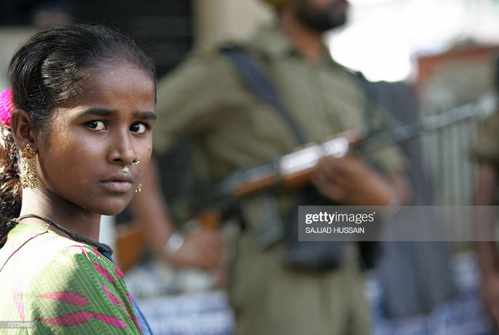 A low-caste - dalit or the oppressed - Hindu girl waits while an Indian Border Security Force Personnel keeps a vigil at a homage site in Mumbai, 06 December 2006. More than 200,000 Hindus at the bottom of India's caste hierarchy gathered in the financial hub Mumbai to pay tribute to their iconic leader B R Ambedkar, a low-caste Hindu who fought against discrimination and who died 50 years ago. In a yearly ritual, low-caste Hindus gather at Ambedkar's 'Chaityabhoomi' (pure-land) memorial in central Mumbai from across western Indian state Maharashtra and neighbouring states. Security forces were on high alert across Mumbai after caste riots claimed four lives last week. AFP PHOTO/ Sajjad HUSSAIN