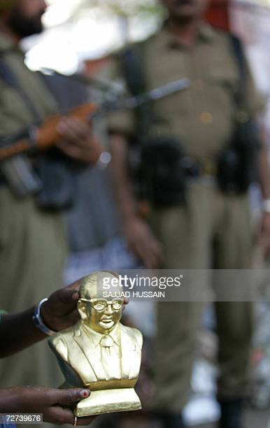A lowcaste Hindu dalit or the oppressed girl shows a statue of B R ambedkar to a customer while Indian Border Security Force Personnel keep a vigil...