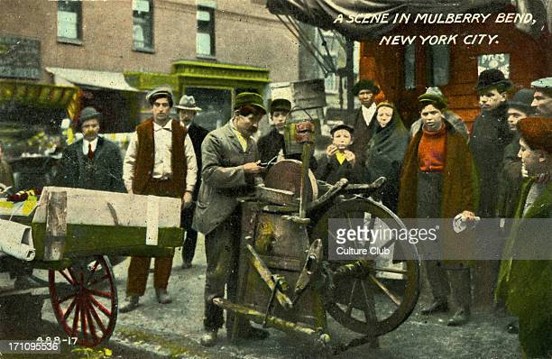 Lower East Side New York A scene in Mulberry Bend 1890s with passersby watching knife grinder Very poor area in late 1890s early 20th century