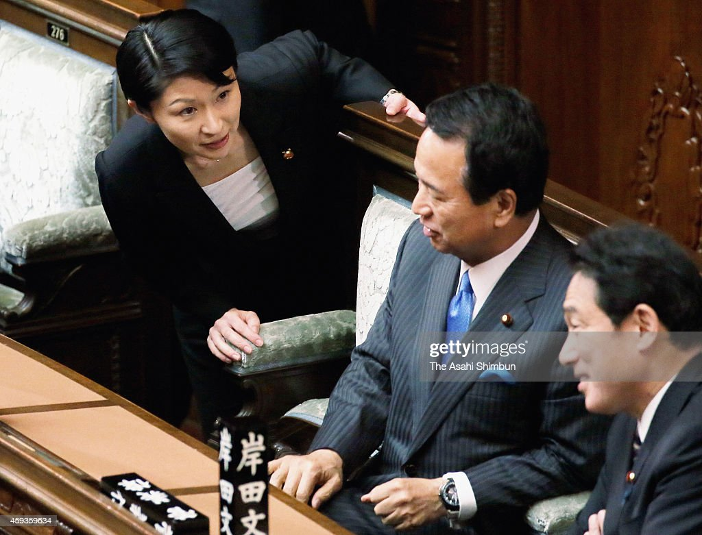 Lower house lawmaker Yuko Obuchi (L) speaks to Economy Rivitalization minister <a gi-track='captionPersonalityLinkClicked' href=/galleries/search?phrase=Akira+Amari&family=editorial&specificpeople=3868034 ng-click='$event.stopPropagation()'>Akira Amari</a> (C) prior to a plenary session in a longtime practice when the chamber is dissolved at the diet building on November 21, 2014 in Tokyo, Japan. The Lower House was dissolved for a snap election, with the postponement of the consumption tax hike and Prime Minister Shinzo Abe's 'Abenomics' economic policy at the center of debate. The official election campaigning will kick off December 2 and people will cast their ballots on December 14, with the chamber's 475 seats up for grabs.