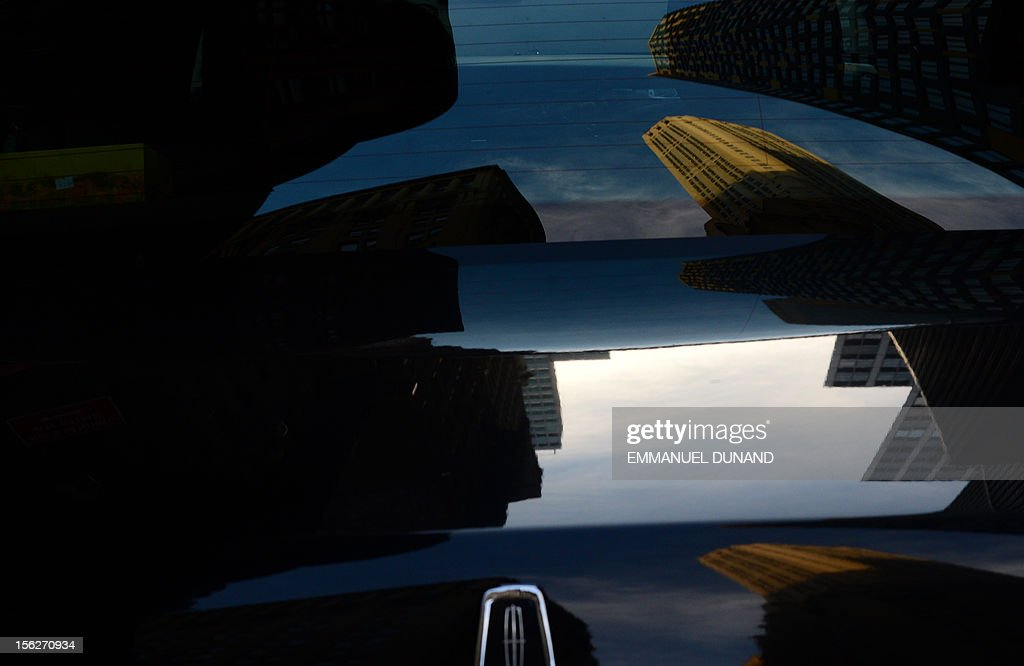 Lower Manhattan's skyline is reflected on the hood of a car in New York on November 12, 2012. AFP PHOTO/Emmanuel DUNAND