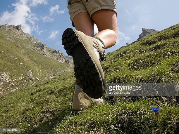 Lower torso of woman hiking up steep mountainside