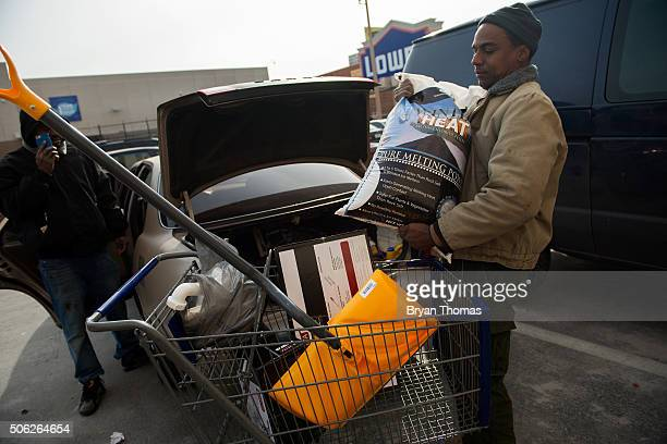 Lowe's customer loads his car with a snow shovel and calcium chloride on January 22 2016 in the Brooklyn borough of New York NY New Yorkers began...