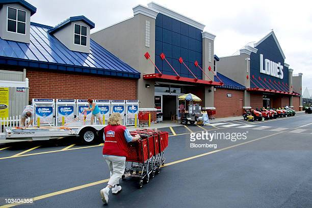 A Lowe's employee collects shopping carts outside a Lowe's store in Wake Forest North Carolina US on Saturday Aug 14 2010 Lowe's Cos the...
