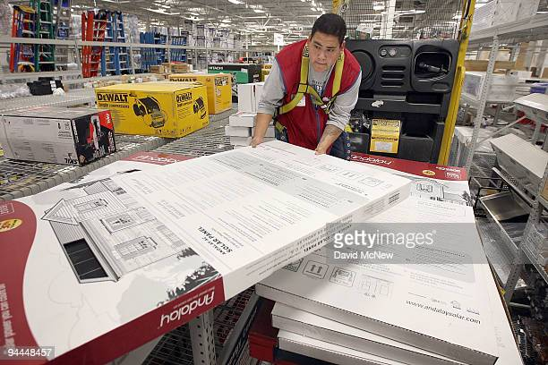 Lowe's employee Luis Legaspi stocks solar electric panels at Lowe's home improvement store on December 14 2009 in West Hills California With growing...