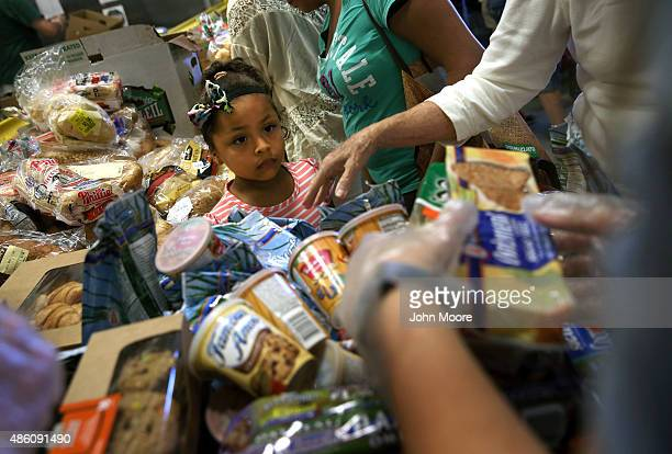Lowincome residents select free bread and produce at the Community Food Bank of New Jersey on August 28 2015 in Egg Harbor New Jersey The food bank...
