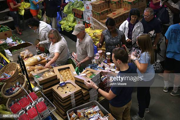 Lowincome residents select fresh bread and produce at the Community Food Bank of New Jersey on August 28 2015 in Egg Harbor New Jersey The food bank...