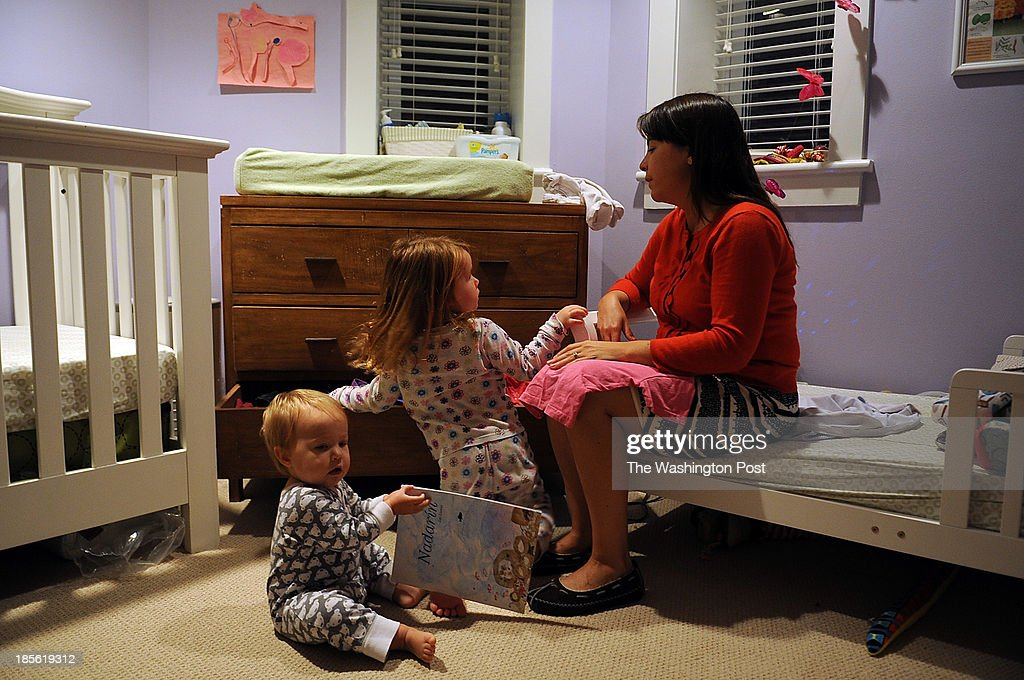 Lowrey Redmond, 37, gets ready two dress her two young daughters, Adele, 3, center, and Mabel, 1, during their morning routine at their family home in Logan Circle.
