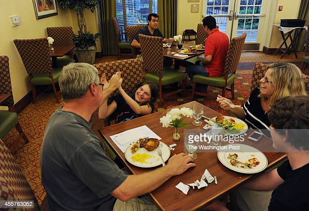Lowry Brooks left jokes his daughter Maggie Brooks left center while eating dinner with his wife Sandy Frain center right and son Jake Brooks bottom...