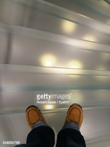 Low-Section Of Man Standing On Acrylic Glass Steps