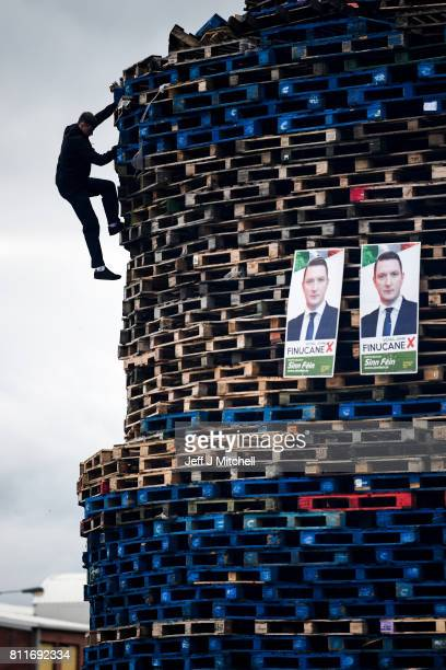 Loyalist climbs the Conway street bonfire built in preparation for the 11th night bonfire on July 10 2017 in Belfast Northern Ireland Tradition holds...