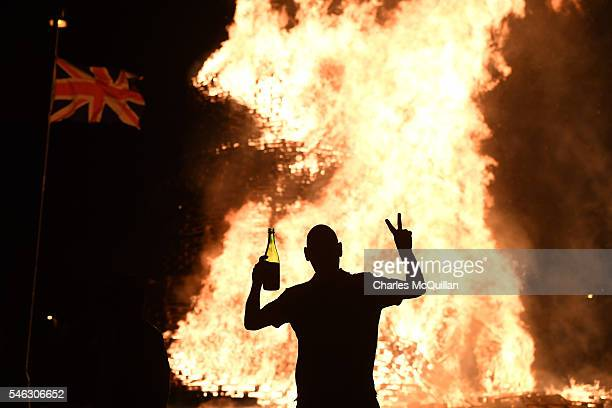 Loyalist is silhouetted as the bonfire is lit on the Shankill estate on July 12 2016 in Belfast Northern Ireland The lighting of the bonfires at...