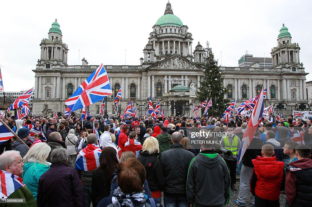 Loyalist march outside Belfast City Hall in protest over Belfast city council's decision to restrict the number of days the British Union Flag can be flown over the city hall in Belfast, Northern Ireland on January 5, 2013. Nine officers were injured and 18 people arrested in fresh violence overnight on the streets of Belfast, police said on January 5. Tensions have risen in the British province since councillors voted on December 3, 2012 to limit the number of days the Union flag can fly over the City Hall to 17, outraging loyalists who believe Northern Ireland should retain strong links to Britain. AFP PHOTO / PETER MUHLY