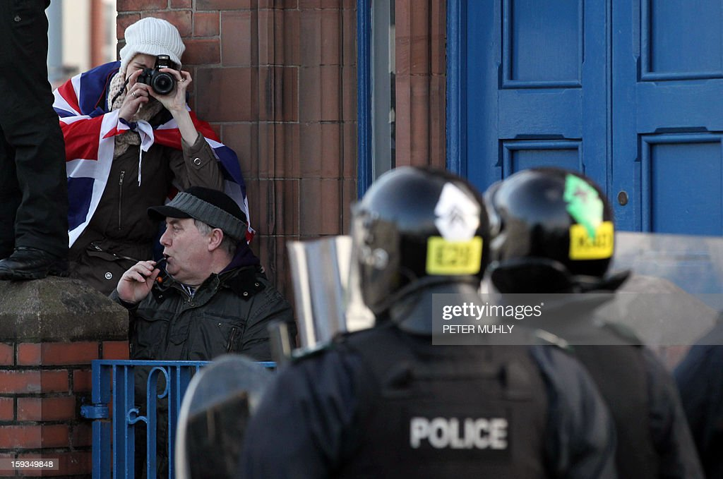 A loyalist protester wrapped in a Union Flag takes a picture as police stand by during violence between, loyalists, nationalists and the police in east Belfast, Northern Ireland on January 12, 2013 after the latest loyalist march against the decision to limit the days on which the Union Flag would be flown over Belfast City Hall. Northern Irish demonstrators loyal to Britain clashed with nationalists and police on Saturday in fresh protests against curbs on flying the British flag, leaving four officers injured, police said. The clashes were the latest to blight the British province after more than five weeks of violent disorder over the flag issue.