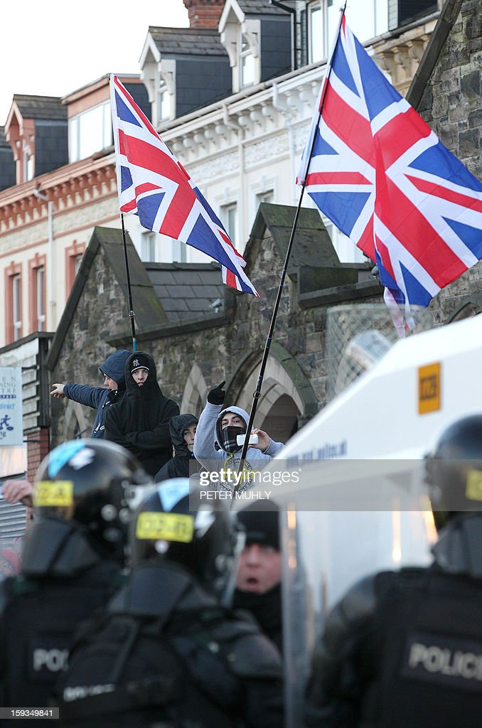 Loyalist protesters waving Union Flags clash with police during violence between, loyalists, nationalists and the police in east Belfast, Northern Ireland on January 12, 2013 after the latest loyalist march against the decision to limit the days on which the Union Flag would be flown over Belfast City Hall. Northern Irish demonstrators loyal to Britain clashed with nationalists and police on Saturday in fresh protests against curbs on flying the British flag, leaving four officers injured, police said. The clashes were the latest to blight the British province after more than five weeks of violent disorder over the flag issue.
