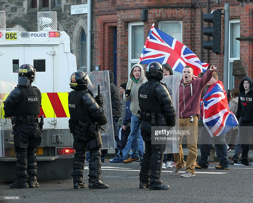 Loyalist protesters waving Union Flags shout at police in riot gear during clashes between, loyalists, nationalists and the police in east Belfast, Northern Ireland on January 12, 2013 after the latest loyalist march against the decision to limit the days on which the Union Flag would be flown over Belfast City Hall. Northern Irish demonstrators loyal to Britain clashed with nationalists and police on Saturday in fresh protests against curbs on flying the British flag, leaving four officers injured, police said. The clashes were the latest to blight the British province after more than five weeks of violent disorder over the flag issue. AFP PHOTO / PETER MUHLY