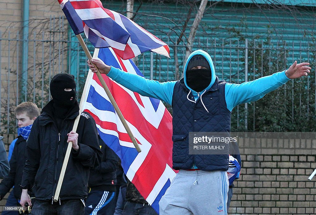 Loyalist protesters waving Union Flags shout during clashes between, loyalists, nationalists and the police in east Belfast, Northern Ireland on January 12, 2013 after the latest loyalist march against the decision to limit the days on which the Union Flag would be flown over Belfast City Hall. Northern Irish demonstrators loyal to Britain clashed with nationalists and police on Saturday in fresh protests against curbs on flying the British flag, leaving four officers injured, police said. The clashes were the latest to blight the British province after more than five weeks of violent disorder over the flag issue.