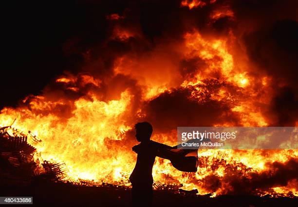 Loyalist youth carrying the Union Jack flag walks past the 11th night bonfire at the New Mossley housing estate on July 12 2015 in Belfast Northern...