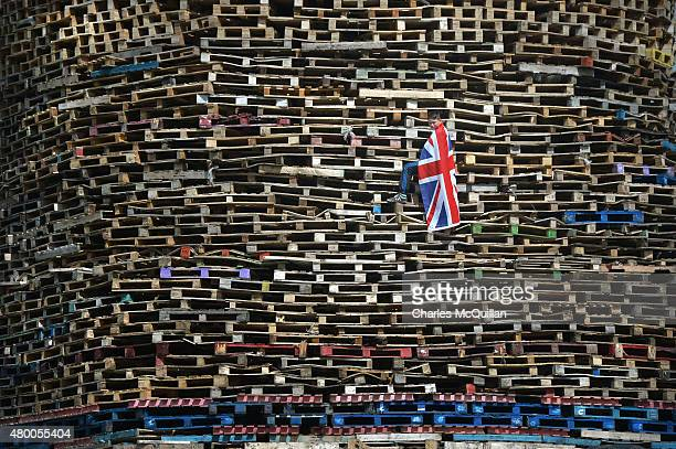 Loyalist youth climbs a large bonfire construct in preparation for their 11th night bonfire at the New Mossley estate on July 9 2015 in Belfast...
