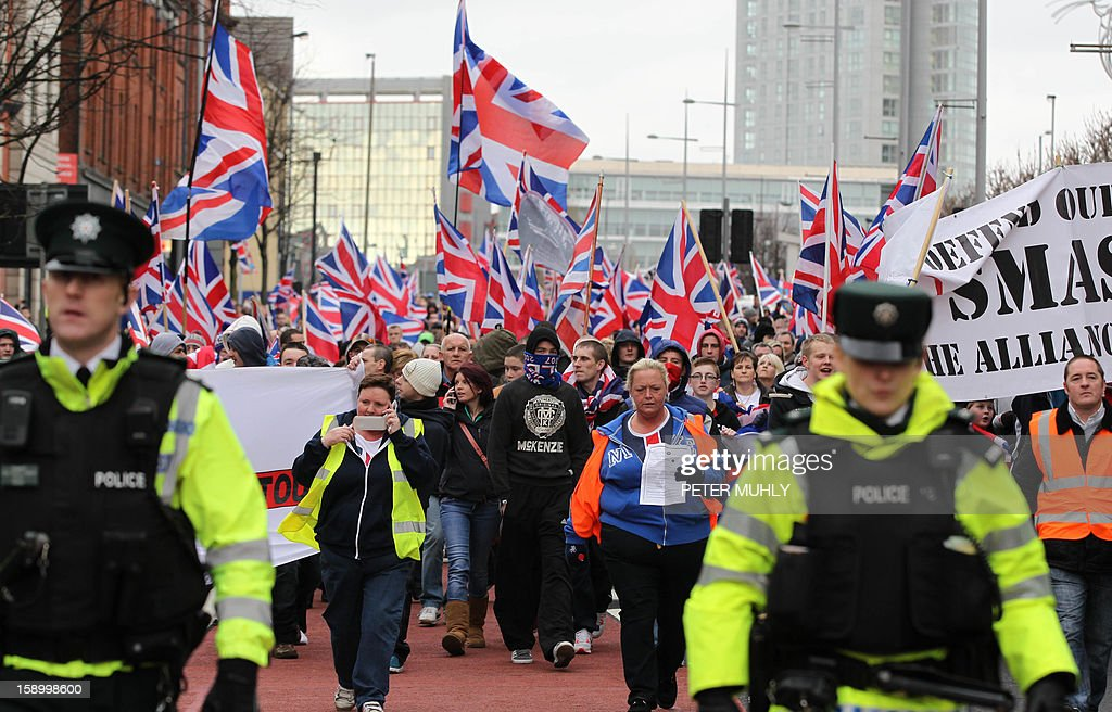 Loyalists flying British Union Flags march outside Belfast City Hall in protest over Belfast city council's decision to restrict the number of days the Union Flag can be flown over the city hall in Belfast, Northern Ireland on January 5, 2013. Nine officers were injured and 18 people arrested in fresh violence overnight on the streets of Belfast, police said on January 5. Tensions have risen in the British province since councillors voted on December 3, 2012 to limit the number of days the Union flag can fly over the City Hall to 17, outraging loyalists who believe Northern Ireland should retain strong links to Britain. AFP PHOTO / PETER MUHLY