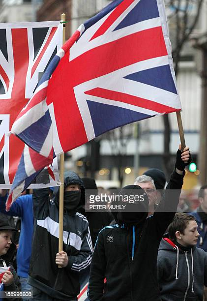 Loyalists flying British Union Flags march outside Belfast City Hall in protest over Belfast city council's decision to restrict the number of days...