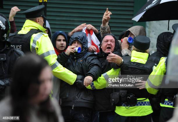 Loyalists shout insults as they protest against a Republican antiinternment parade on August 10 2014 in Belfast Northern Ireland The annual...