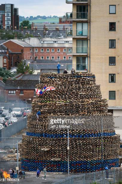 Loyalists sit on the Sandy Row bonfire being built in preparation for the 11th night bonfire on July 10 2017 in Belfast Northern Ireland Tradition...