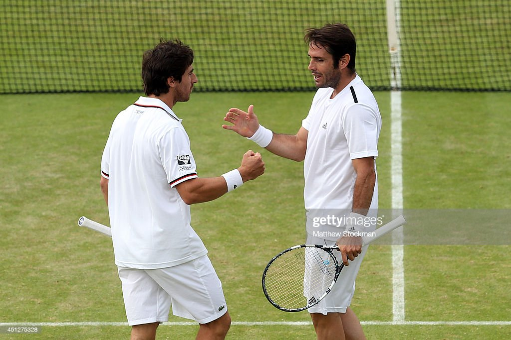 l-r <a gi-track='captionPersonalityLinkClicked' href=/galleries/search?phrase=Pablo+Cuevas&family=editorial&specificpeople=822084 ng-click='$event.stopPropagation()'>Pablo Cuevas</a> of Uruguay and <a gi-track='captionPersonalityLinkClicked' href=/galleries/search?phrase=David+Marrero&family=editorial&specificpeople=5357971 ng-click='$event.stopPropagation()'>David Marrero</a> of Spain during their Gentlemen's Doubles first round match against Colin Fleming and Ross Hutchins of Great Britain on day four of the Wimbledon Lawn Tennis Championships at the All England Lawn Tennis and Croquet Club at Wimbledon on June 26, 2014 in London, England.