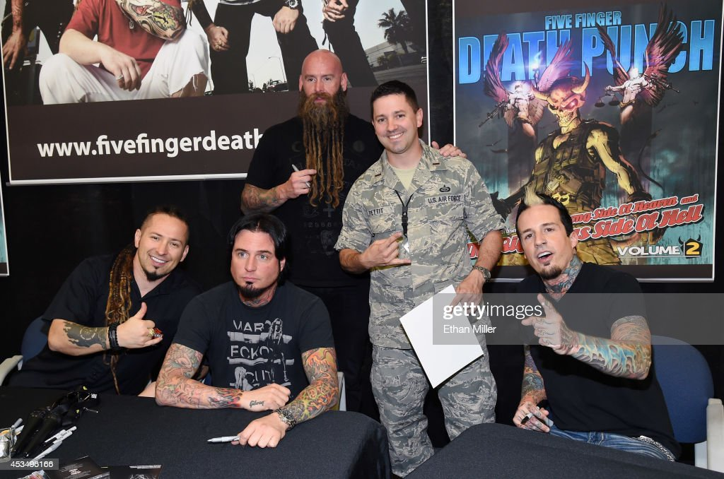 Lt. Brian Pettit (4th L) poses for a photo with (L-R) guitarists Zoltan Bathory and Jason Hook, bassist Chris Kael and drummer Jeremy Spencer of Five Finger Death Punch at Nellis Air Force Base as the band highlights its campaign to raise awareness about veterans suffering from post-traumatic stress disorder (PTSD), in part by launching the video 'Wrong Side of Heaven,' that deals with the subject on August 11, 2014 in Las Vegas, Nevada.