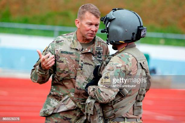 Lt Gen Jeff Buchanan talks to a US Army helicopter crewmember before taking off from Barranquitas after a supplies delivery mission for residents...