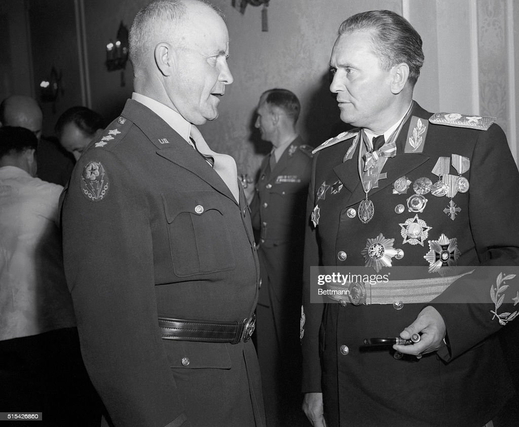 Lt. Gen. John C.H. Lee, (left) Commanding General, Mtousa , has a serious conversation with Marshal Tito, attired in dress uniform and many medals, during a reception given by Tito in Belgrade on the anniversary of V-E Day, May 9, 1946. Also present at the reception were members of an UNRRA Committee, currently on an inspection tour in Yugoslavia.