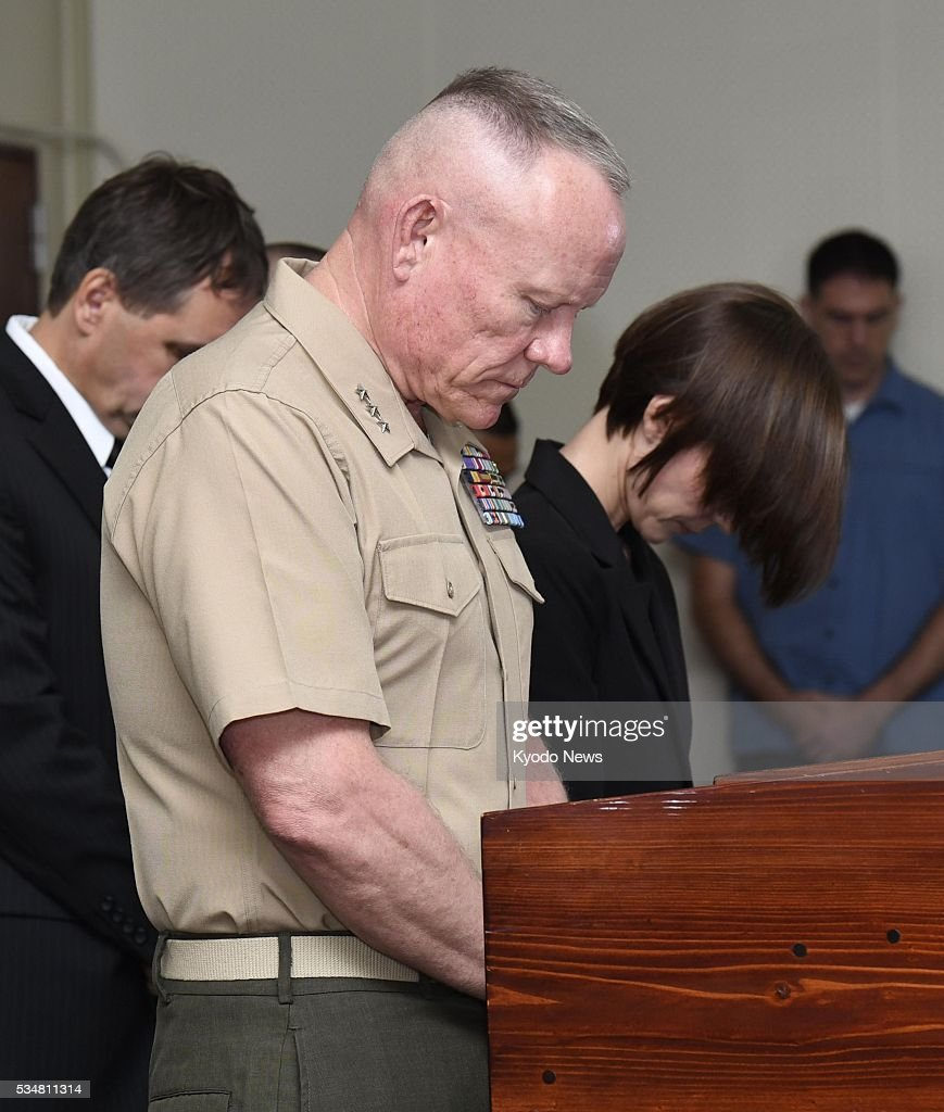 Lt. Gen. Lawrence Nicholson (C) offers a silent prayer to mourn the death of a 20-year-old Japanese woman, at a press conference at Camp Foster in Okinawa Prefecture on May 28, 2016. The military commander expressed his shock and regret at the incident over which an American base worker, who is a former Marine, has been arrested, and explained measures to tighten discipline among U.S. forces.