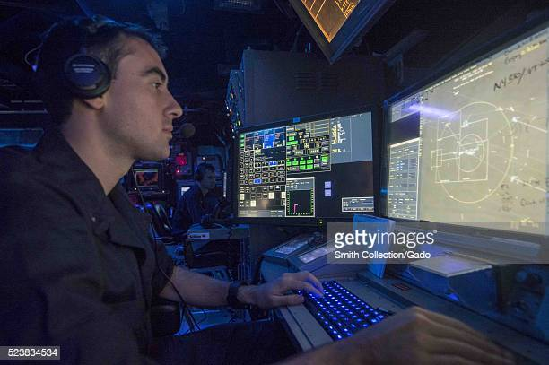 Lt jg Michael Cornish from Omaha Neb stands watch in the combat information center aboard the guidedmissile cruiser USS Normandy CG 60 during an...