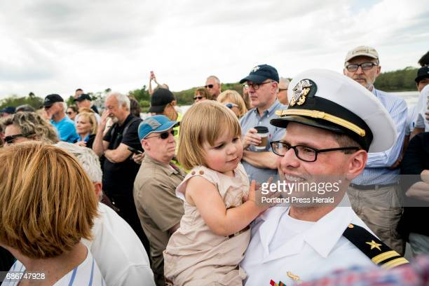Lt Michael Bingham of the US Navy and a resident of Kennebunk holds his son Silas as they and hundreds of others take in the dedication of the new...