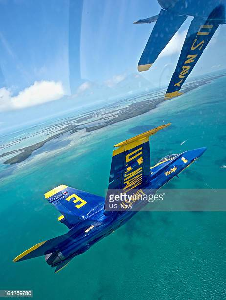 Lt Nate Barton flies his Blue Angels fighter jet at left in formation during practice March 21 2013 over the lower Florida Keys Florida The Blue...
