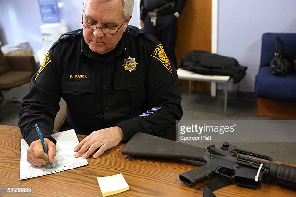 Lt Ray Mesek registers a Colt AR15 at a gun buyback event at the Bridgeport Police Department's Community Services Division on December 22 2012 in...