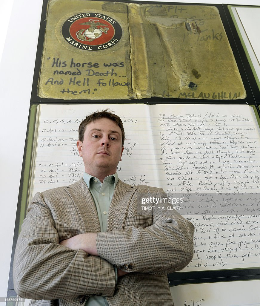 Lt. Tim McLaughlin, who drove a Marine Corps tank into Iraq in 2003, is seen at an exhibit displaying 36 pages from his diaries, each page blown up to poster-size at the The Bronx Documentary Center in New York March 14, 2013. Timed to the 10th anniversary of the invasion, the exhibit centers around large-format reprints of a diary written by Lt. Tim McLaughlin, who was at the Pentagon on 9/11, whose battalion spearheaded the Iraq invasion, and whose American flag was placed over a famous statue of Saddam Hussein in Baghdad's Firdos Square. The exhibit which opens March 14, will include the iconic flag, which Tim kept in a safe deposit box when he returned home from Iraq. It will also feature photos of the invasion by Gary Knight and texts by Peter Maass. AFP PHOTO / TIMOTHY A. CLARY
