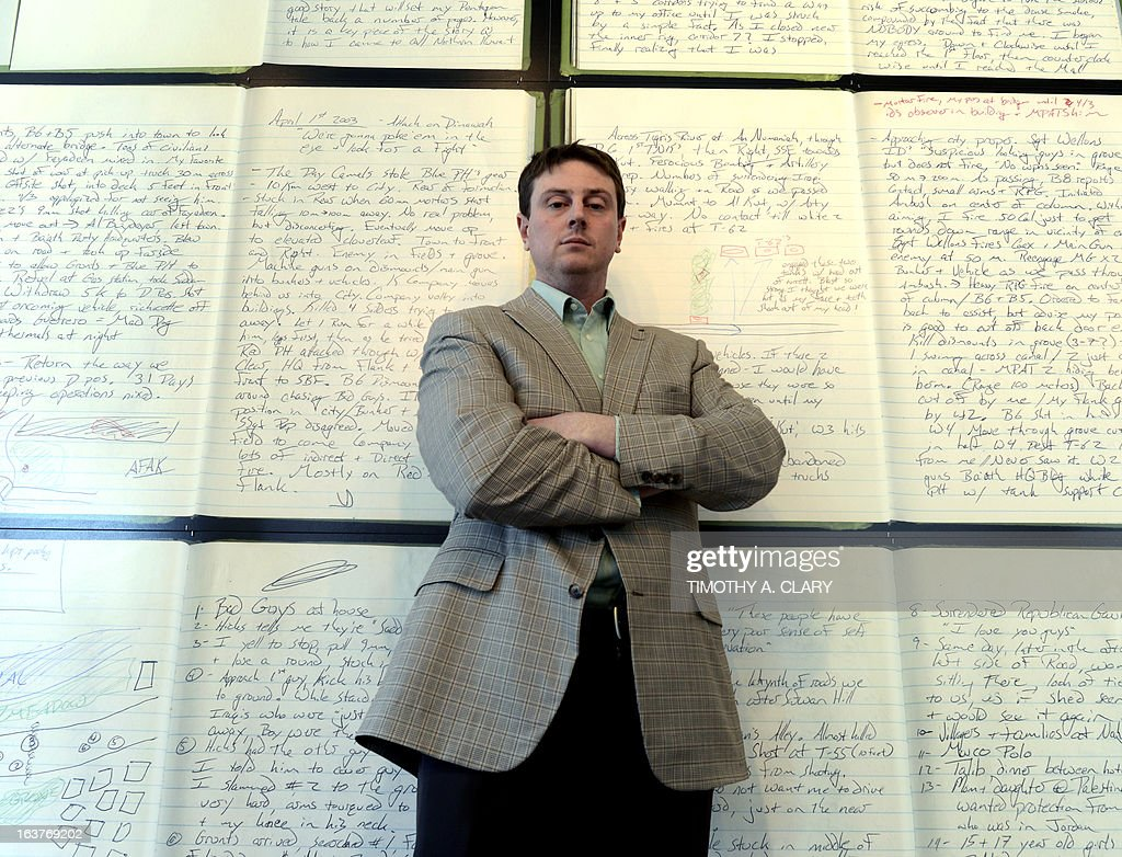 Lt. Tim McLaughlin, who drove a Marine Corps tank into Iraq in 2003, is seen at an exhibit displaying 36 pages from his diaries, each page blown up to poster-size at the The Bronx Documentary Center in New York March 14, 2013. Timed to the 10th anniversary of the invasion, the exhibit centers around large-format reprints of a diary written by Lt. Tim McLaughlin, who was at the Pentagon on 9/11, whose battalion spearheaded the Iraq invasion, and whose American flag was placed over a famous statue of Saddam Hussein in Baghdad's Firdos Square. The exhibit which opens March 14, will include the iconic flag, which Tim kept in a safe deposit box when he returned home from Iraq. It will also feature photos of the invasion by Gary Knight and texts by Peter Maass.