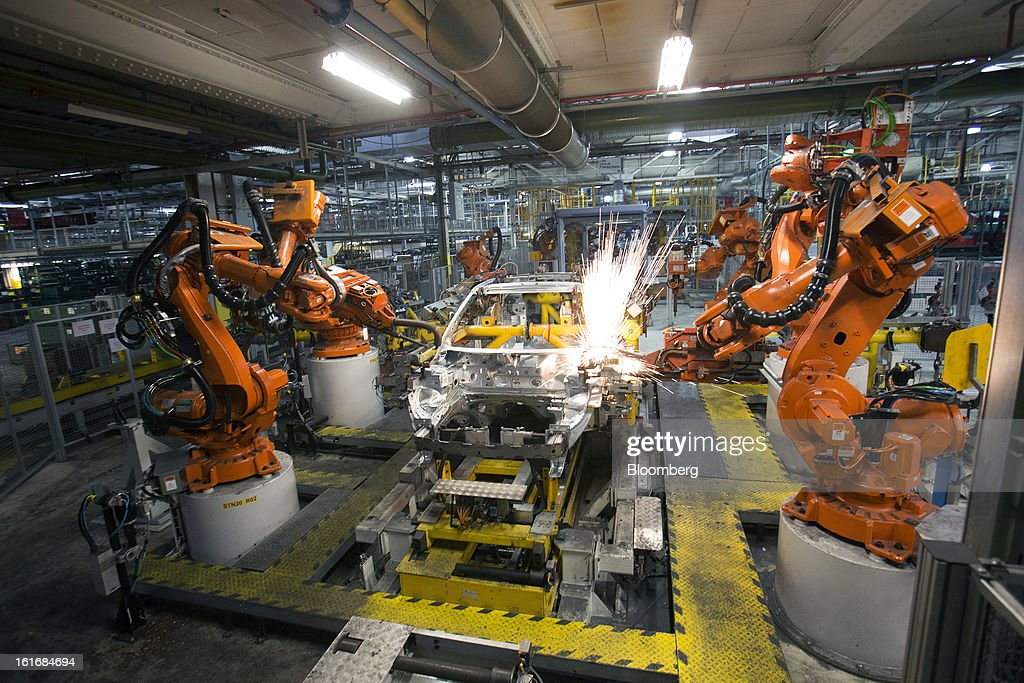 ABB Ltd. robotic arms weld the aluminum panels of an SUV automobile body shell as it travels along the production line at Jaguar Land Rover Plc's assembly plant, a unit of Tata Motors Ltd., in Halewood, U.K., on Wednesday, Feb. 13, 2013. Carmakers from Ford Motor Co. to Audi AG and Jaguar Land Rover Plc are using record amounts of aluminium to replace heavier steel, providing relief to producers of the metal confronting excess supplies and depressed prices. Photographer: Simon Dawson/Bloomberg via Getty Images