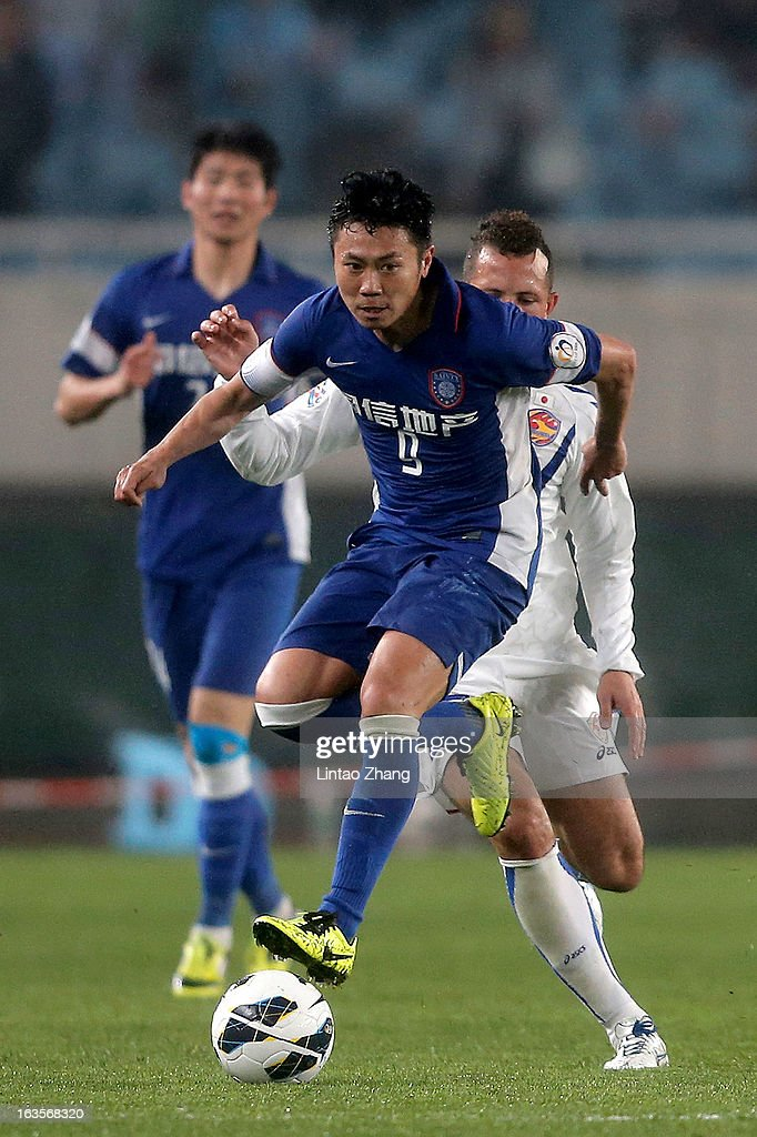 Lu Baofei (C) of Jiangsu Sainty challenges Diogo of Vegalta Sendaion during the AFC Champions League match between Jiangsu Sainty and Vegalta Sendai at Nanjing Olympic Sports Center Stadium on March 12, 2013 in Nanjing, China.