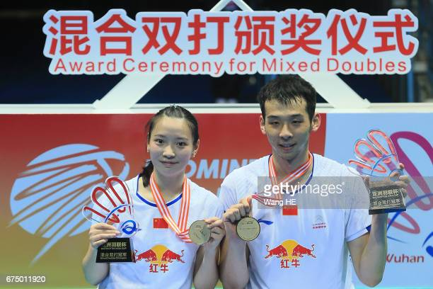 Lu Kai of and Huang Yaqiong of China pose with their gold medals on the podium after winning the their mixed doubles final match against Sapslewiree...
