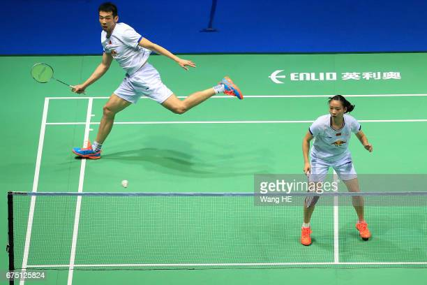 Lu Kai of China hits a return next to his partner Huang Yaqiong during their mixed doubles final match against Sapslewiree Taerattan and Dechapol...