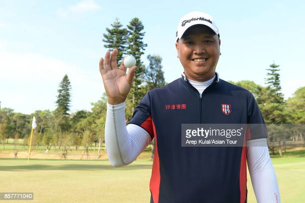 Lu Weichih of Taiwan pose with his ball after making a holeone at holes 11th during round one for the Yeangder Tournament Players Championship at...