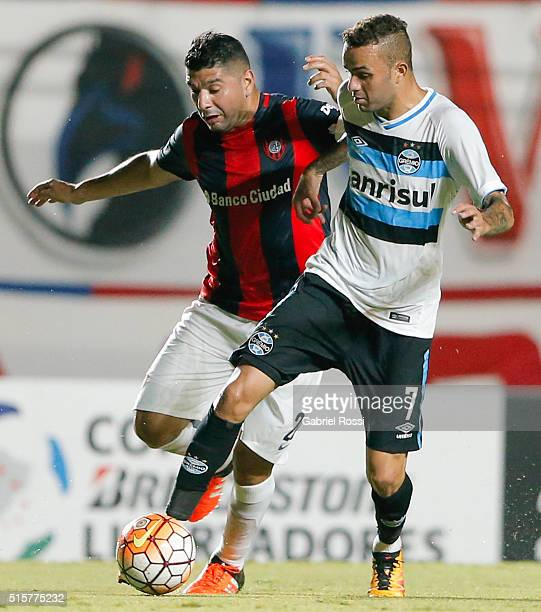 Luan of Gremio fights for the ball with Nestor Ortigoza of San Lorenzo during a match between San Lorenzo and Gremio as part of Group 6 of Copa...