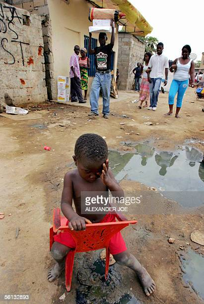 An Angolan child sits in the street in the poor part of Luanda 10 November 2005 Angola is celebrating the country's 30 years of independence from...