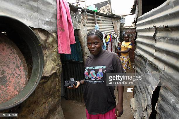 An Angolan mother holds a handfull of coal to make a fire to cook lunch for the family outside her home in the poor part of Luanda 10 November 2005...