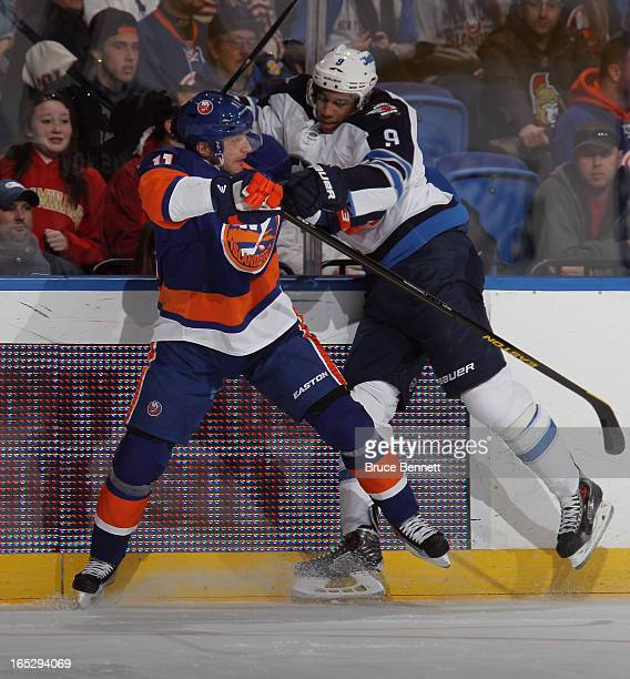 Lubomir Visnovsky of the New York Islanders and Evander Kane of the Winnipeg Jets hit the boards at the Nassau Veterans Memorial Coliseum on April 2...