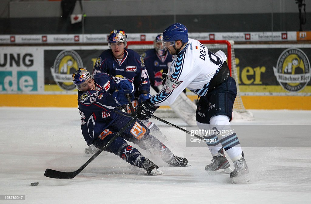Lubor Dibelka (L) and Felix Petermann (C) of EHC Red Bull Munich in action with Thomas Dolak of Hamburg Freezers during the DEL ice hockey game between Red Bull Munich and Hamburg Freezers at Olympia Eishalle on December 28, 2012 in Munich, Germany.
